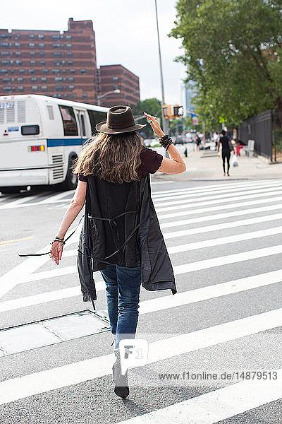 Stilvolle reife Frau in Trilby-Tracht beim Schlendern über den Vorstadt-Fußgängerüberweg  Rückansicht