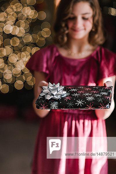 Mädchen hält Weihnachtsgeschenk