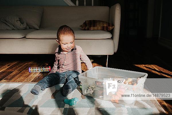 Kleiner Junge sitzt auf dem Wohnzimmerboden und spielt mit Spielzeug