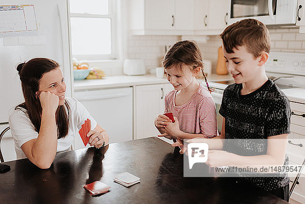 Mother and children playing cards in kitchen