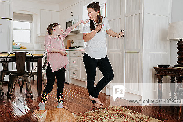 Girl extending hand to mother in kitchen