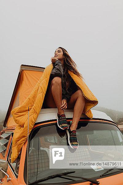 Junge Frau schaut von der Spitze eines Wohnmobils am Strand hinaus  Jalama  Kalifornien  USA