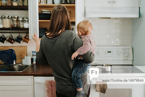 Mother carrying baby son preparing food in kitchen  rear view