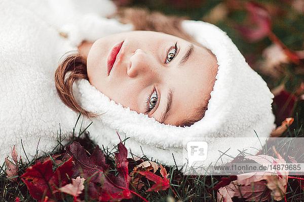 Mädchen in weißem Kapuzen-Oberteil auf Gras zwischen Herbstlaub liegend  Portrait
