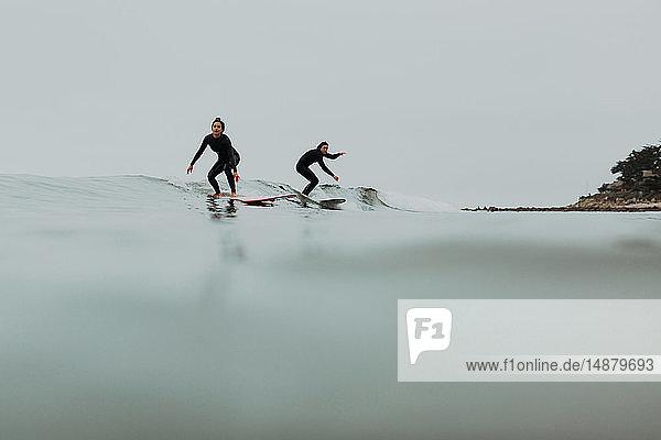 Junges Surferpaar beim Surfen auf ruhiger  nebliger See  Ventura  Kalifornien  USA