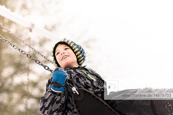Junge mit Strickmütze schwingt im Winter auf der Spielplatzschaukel