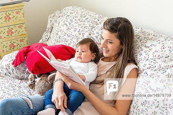 Mutter liest einem Mädchen auf dem Sofa vor
