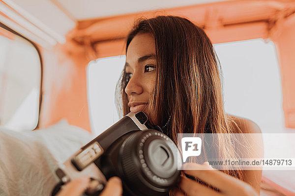 Junge Frau  die eine Sofortbildkamera auf dem Rücksitz eines Wohnmobils hochhält  Jalama  Kalifornien  USA