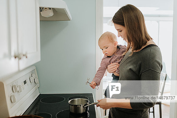 Mother carrying baby son while cooking at hob