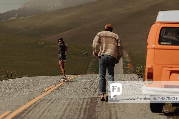 Junges Skateboardfahrerpaar beim Skateboarden auf einer Landstraße neben einem Wohnmobil  Jalama  Kalifornien  USA