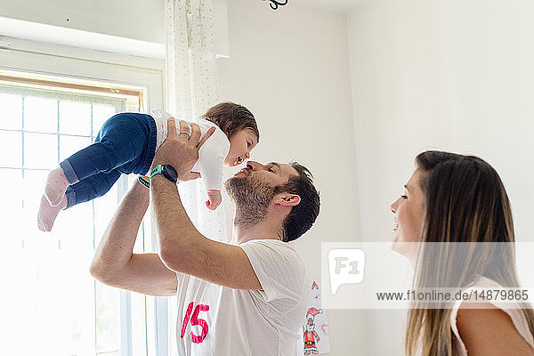 Parents playing with baby girl at home