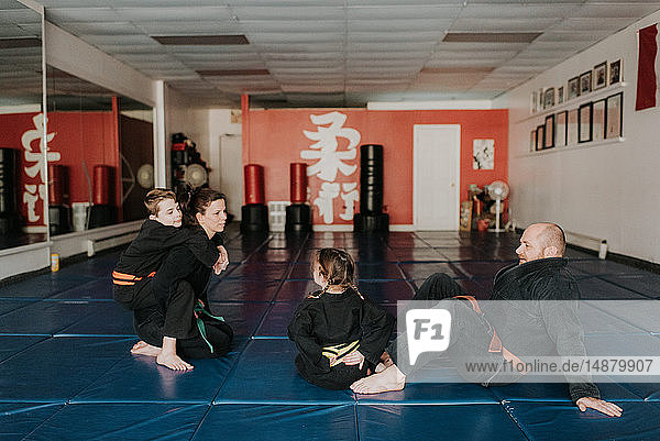 Coaches and students resting in martial arts studio
