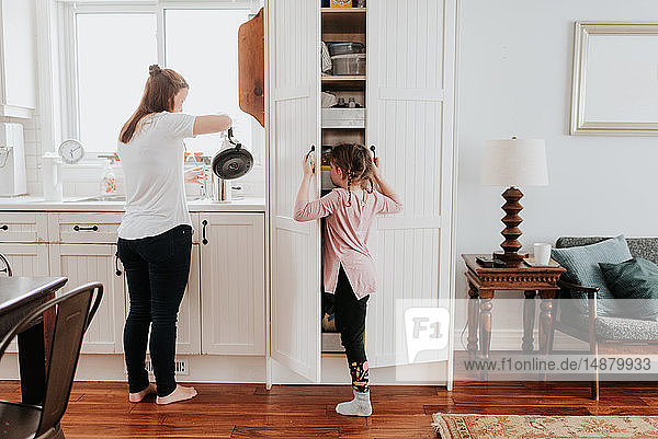 Mother pouring hot water  girl looking into cabinet in kitchen