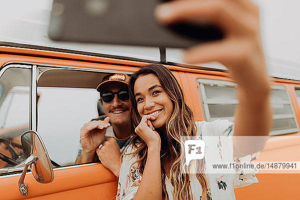 Young couple on road trip in recreational vehicle taking smartphone selfie  portrait  Jalama  California  USA