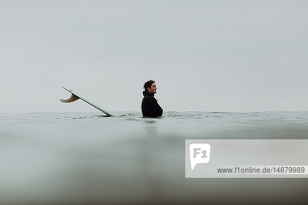 Junger männlicher Surfer auf dem Surfbrett in nebliger See  Ventura  Kalifornien  USA