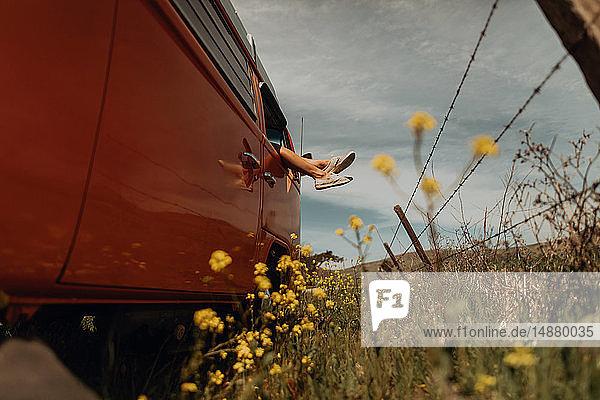 Die Beine einer jungen Frau aus dem Fenster eines Wohnmobils am Rand einer Landstraße  Jalama  Kalifornien  USA