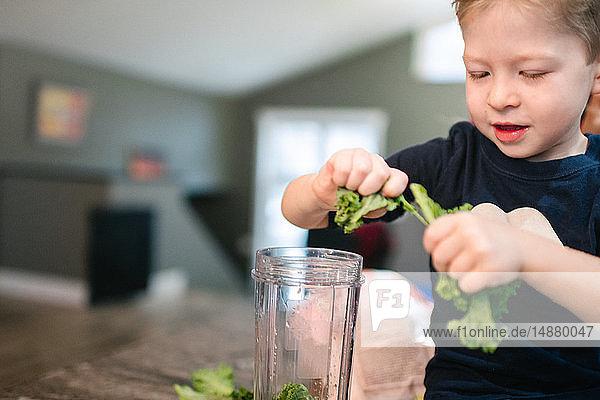 Kleinkind schält Gemüse in den Mixer