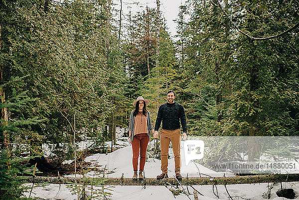 Couple standing on fallen tree trunk in forest  Tobermory  Canada