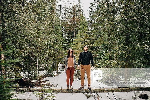 Ehepaar steht auf umgestürztem Baumstamm im Wald,  Tobermory,  Kanada