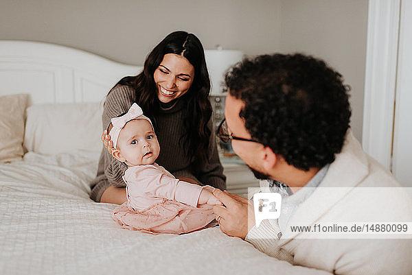 Ehepaar mit kleiner Tochter im Bett im Schlafzimmer