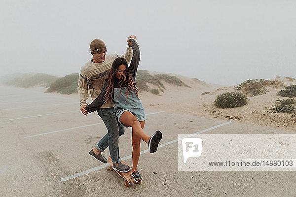 Junges Paar hält Händchen und teilt sich ein Skateboard auf einem Strandparkplatz  Jalama  Kalifornien  USA