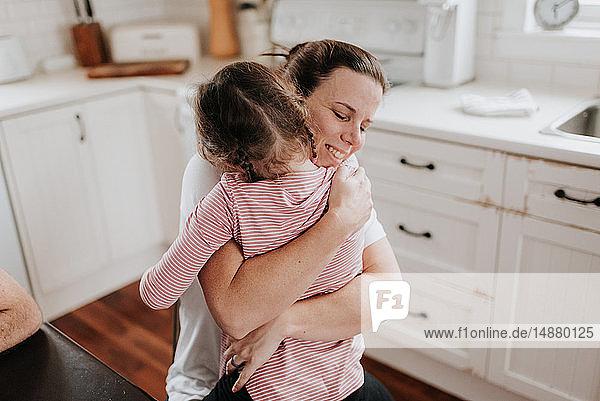 Mutter umarmt Tochter in der Küche
