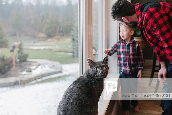 Vater und Sohn unterhalten sich zu Hause am Fenster