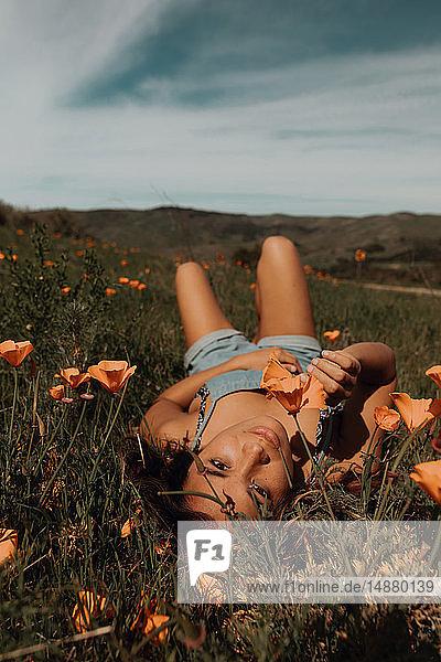 Junge Frau liegt im Feld von Wildblumen  Porträt  Jalama  Kalifornien  USA