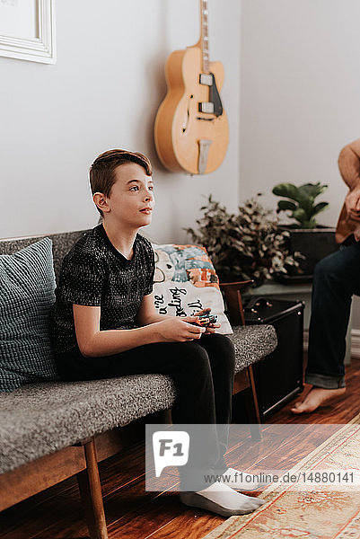Boy playing video game on couch