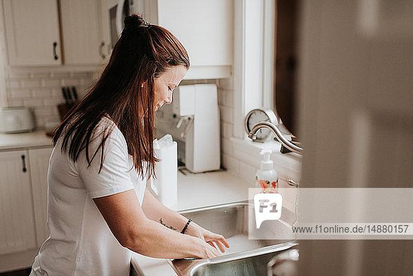 Frau spült in der Küchenspüle