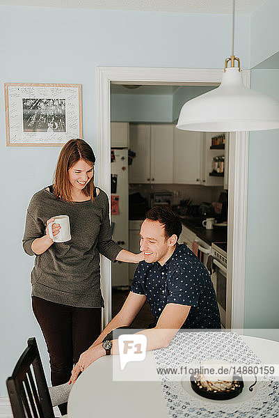 Mid adult couple taking a coffee break at kitchen table