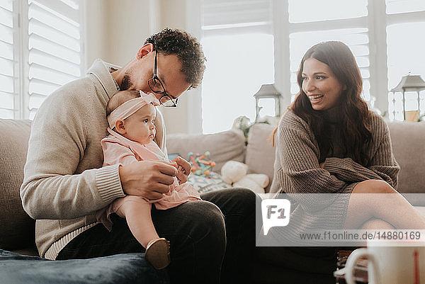 Paar spielt mit der kleinen Tochter auf dem Sofa