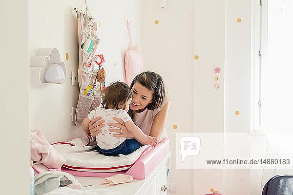Mutter spricht mit Mädchen auf dem Wickeltisch