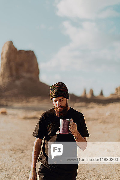 Man with mug of tea in desert  Trona Pinnacles  California  US