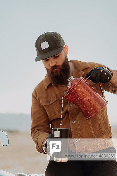 Mann gießt heißes Wasser in Becher  Trona Pinnacles  Kalifornien  USA