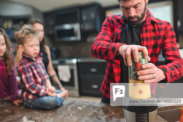 Mutter und Kinder sehen zu  wie der Vater in der Küche Gemüse mischt