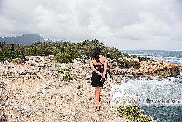 Frau geht mit einem Handy in der Hand  Shipwreck Beach  Kauai  Hawaii