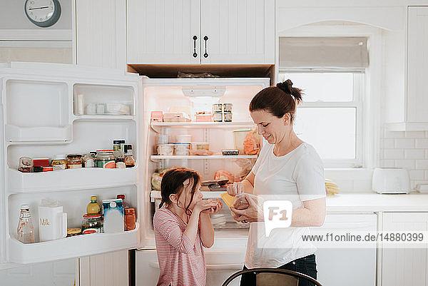 Mutter gibt Tochter Wurst aus dem Kühlschrank