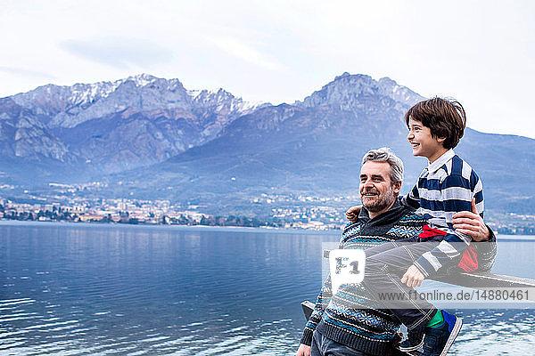 Junge und Vater sitzen am Comer See am Pierzaun. Onno  Lombardei  Italien