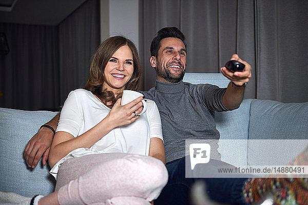 Junges Paar sitzt abends auf dem Sofa und sieht fern