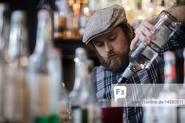 Barman pouring spirit bottle in traditional Irish public house