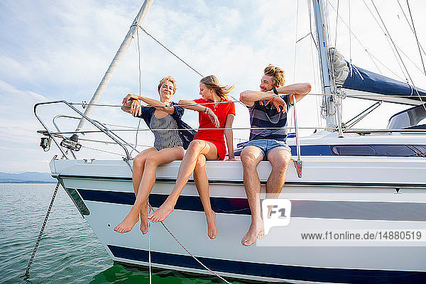 Mature woman and young adults sitting on sailboat on Chiemsee lake  Bavaria  Germany