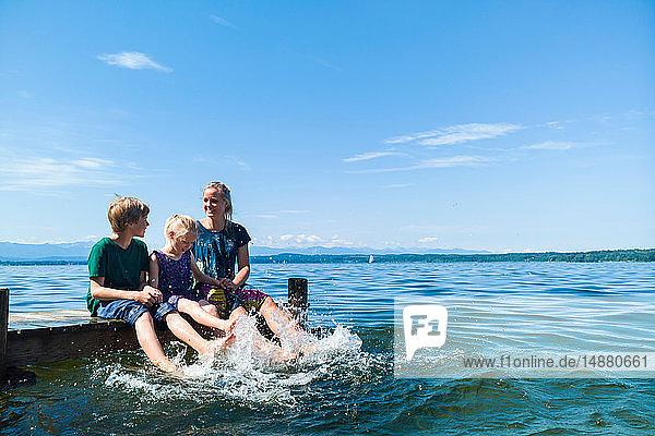 Mutter und Kinder kühlen Füße im Wasser,  Starnberger See,  Bayern,  Deutschland