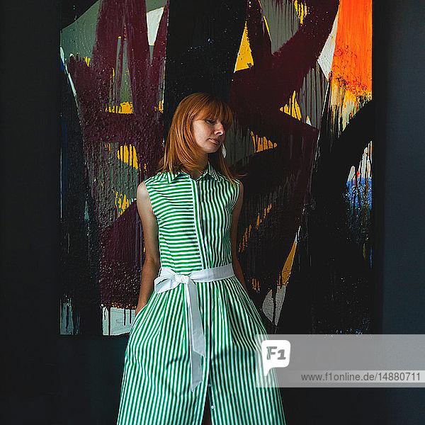 Frau in grünem Sommerkleid neben moderner Malerei