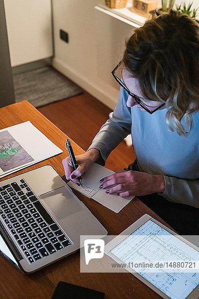 Frau macht Notizen von Laptop und digitalem Tablet