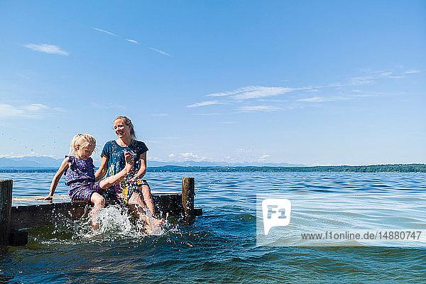 Mutter und Tochter kühlen Füße im Wasser  Starnberger See  Bayern  Deutschland