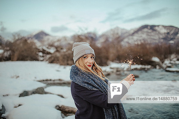 Frau mit Strickmütze mit Wunderkerze am schneebedeckten Flussufer  Porträt  Orta  Piemont  Italien