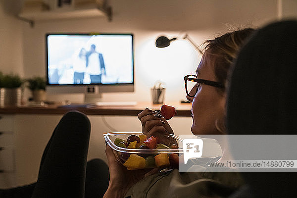 Woman relaxing in front of TV with fruit salad