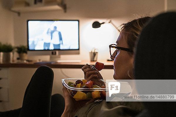 Frau entspannt sich vor dem Fernseher mit Obstsalat