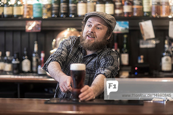 Barman serving beer from bar in traditional Irish public house